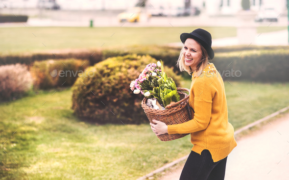 Young woman with flowers in a basket in sunny spring town. - Stock Photo - Images