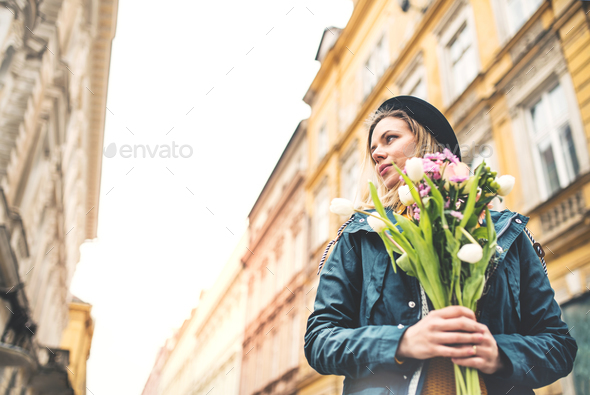 Young woman with flowers in sunny spring town. - Stock Photo - Images
