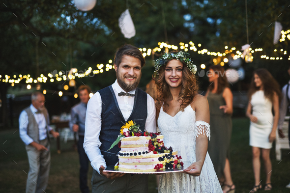 Bride and groom holding a cake at wedding reception outside in the backyard. - Stock Photo - Images