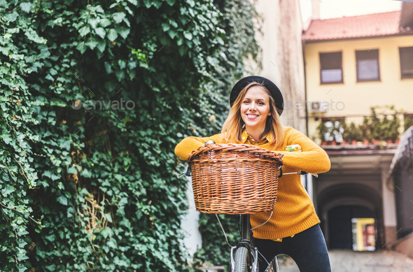 Young woman with bicycle in sunny spring town. - Stock Photo - Images