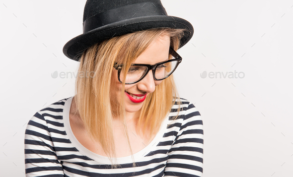 Portrait of a young beautiful woman with a black hat in studio. Close up. - Stock Photo - Images