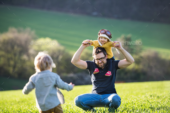 A father with his toddler children having fun outside, spring nature. - Stock Photo - Images