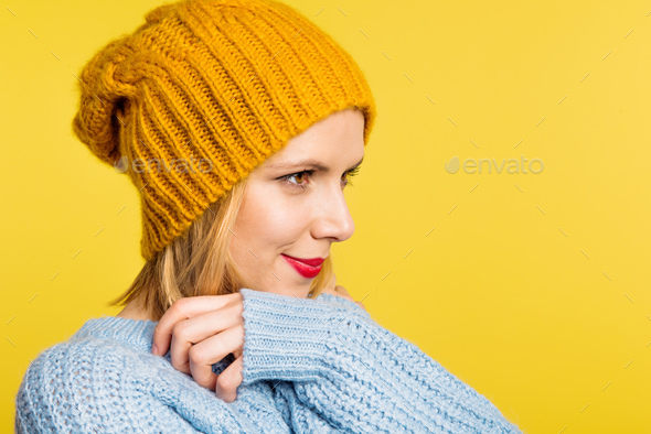 Portrait of a young beautiful woman with a woolen hat in studio on a yellow background. - Stock Photo - Images