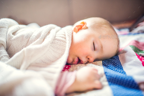 A toddler girl sleeping on a bed at home. - Stock Photo - Images