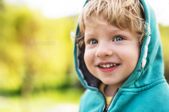 A happy toddler boy outside in spring nature. Close up. - Stock Photo - Images