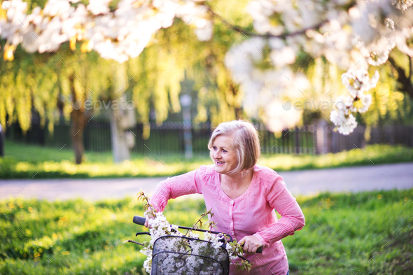Beautiful senior woman with bicycle outside in spring nature. - Stock Photo - Images
