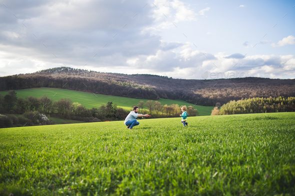 A father with his toddler son running outside in spring nature. - Stock Photo - Images
