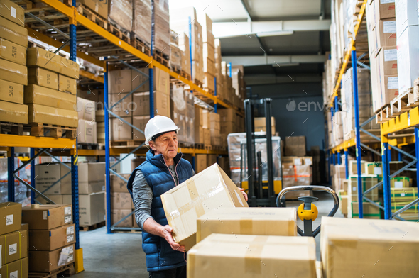 Senior male warehouse worker unloading boxes from a pallet truck. - Stock Photo - Images