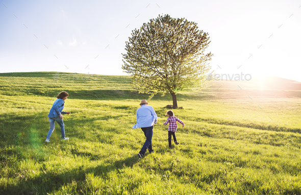 A small girl with her senior grandparents playing outside in nature. - Stock Photo - Images