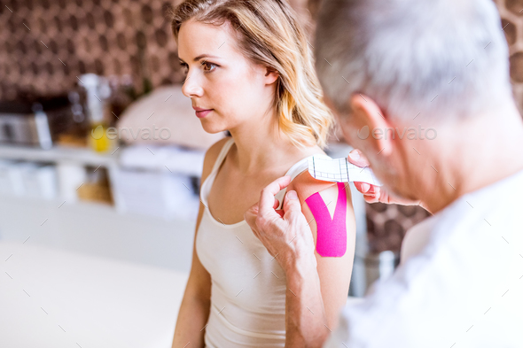 Senior male physiotherapist applying tape on a female patient. Close up. - Stock Photo - Images
