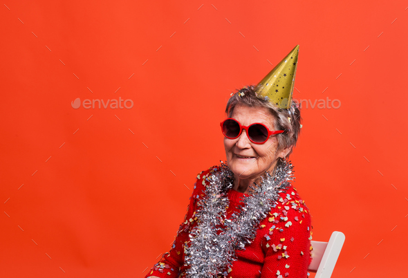 Portrait of a senior woman in studio on a red background. Party concept. - Stock Photo - Images