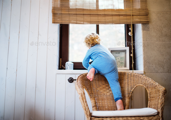 Toddler boy in a dangerous situation at home. - Stock Photo - Images
