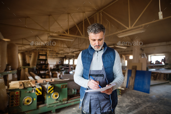 A man worker in the carpentry workshop, making plans. - Stock Photo - Images