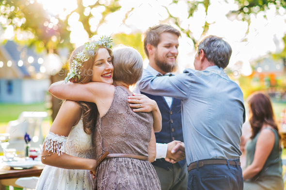 Guests congratulating bride and groom at wedding reception outside in the backyard. - Stock Photo - Images