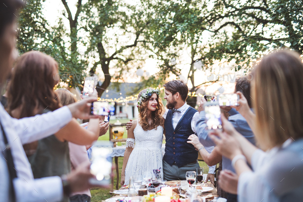 Guests with smartphones taking photo of bride and groom at wedding reception outside. - Stock Photo - Images