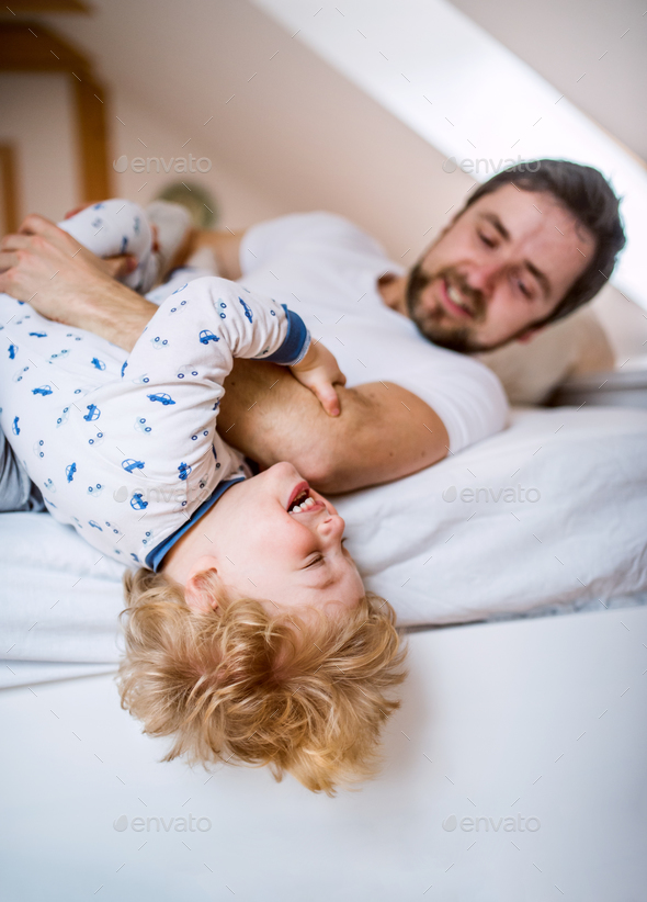 Father with a toddler boy having fun in bedroom at home at bedtime. - Stock Photo - Images