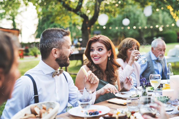 Guests eating at the wedding reception outside in the backyard. - Stock Photo - Images