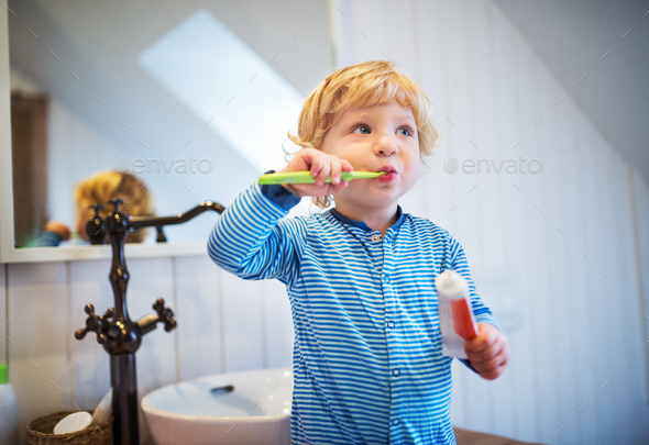 Cute toddler boy brushing his teeth in the bathroom. - Stock Photo - Images