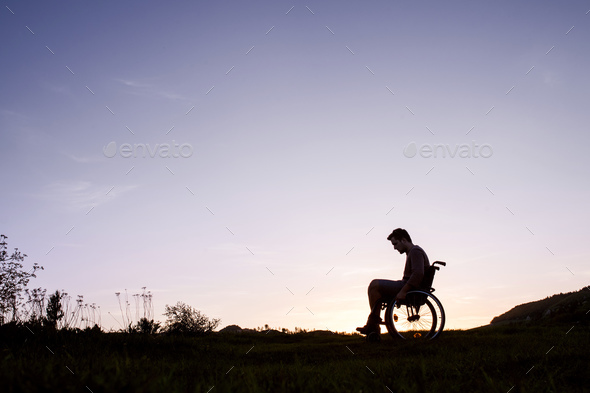 A young man in wheelchair in nature in the evening. - Stock Photo - Images