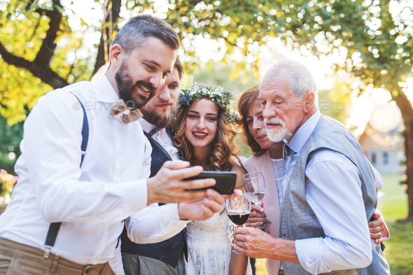 Bride, groom and guests with smartphones taking selfie outside at wedding reception. - Stock Photo - Images