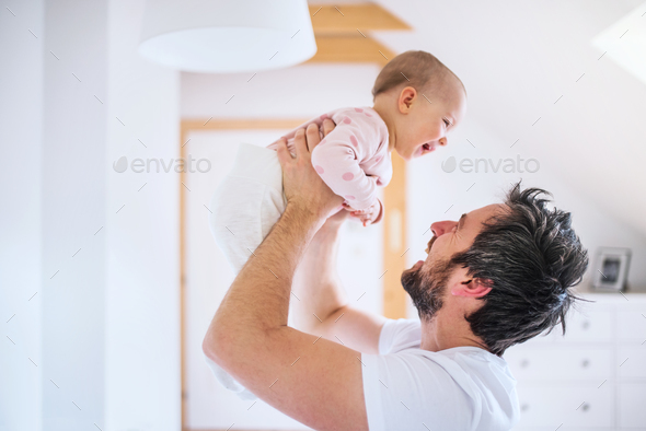 Father with a toddler girl in bedroom at home, having fun. - Stock Photo - Images