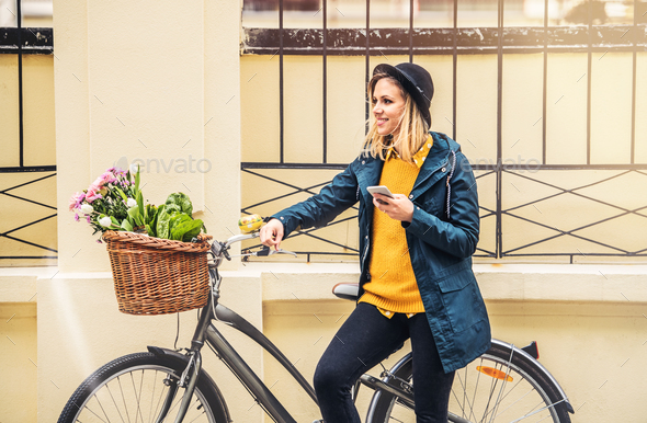 Young woman with bicycle and smartphone in sunny spring town. - Stock Photo - Images