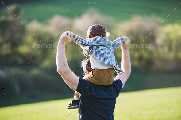 A father giving toddler son piggyback ride outside in spring nature. - Stock Photo - Images