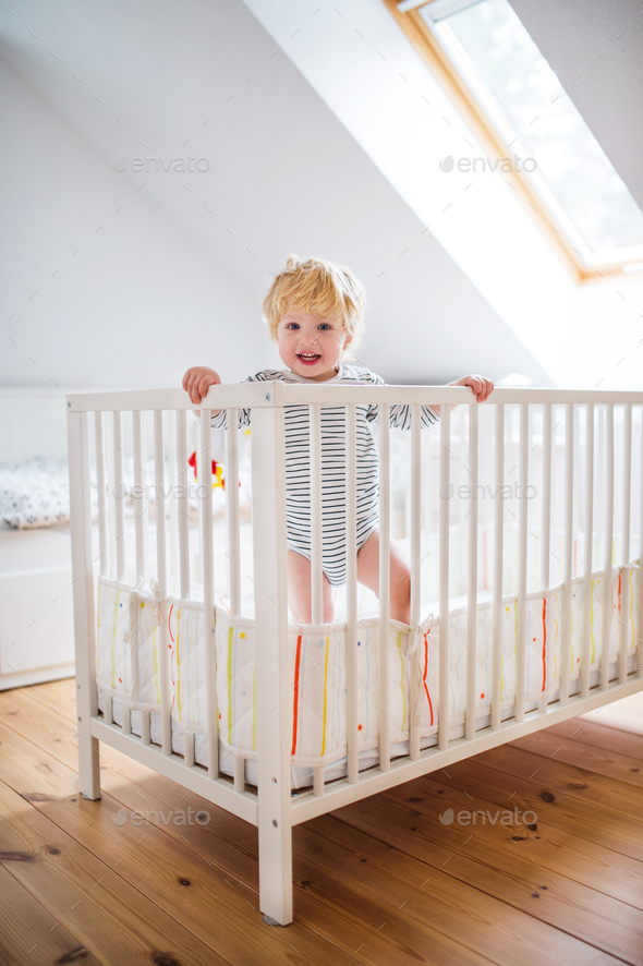 Cute toddler boy standing in a cot at home. - Stock Photo - Images