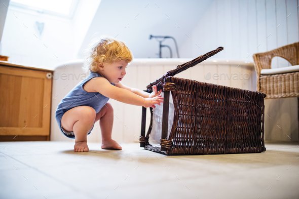 Toddler boy with a laundry basket in the bathroom. - Stock Photo - Images