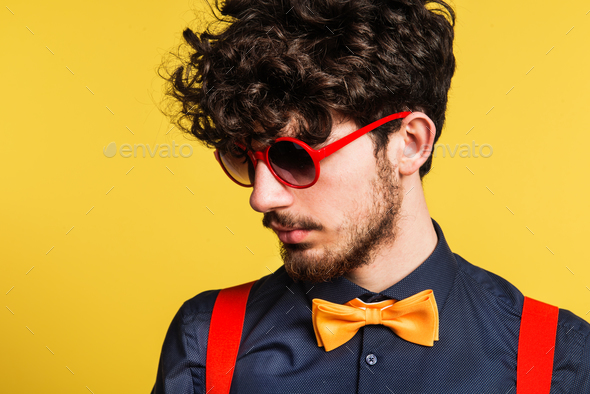 Portrait of a young man in a studio on a yellow background. - Stock Photo - Images