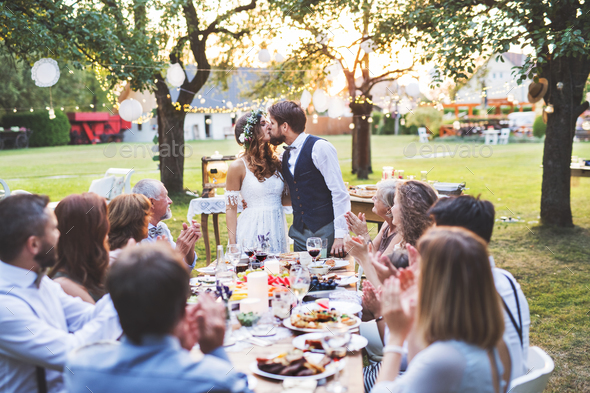 Bride and groom with guests at wedding reception outside in the backyard. - Stock Photo - Images