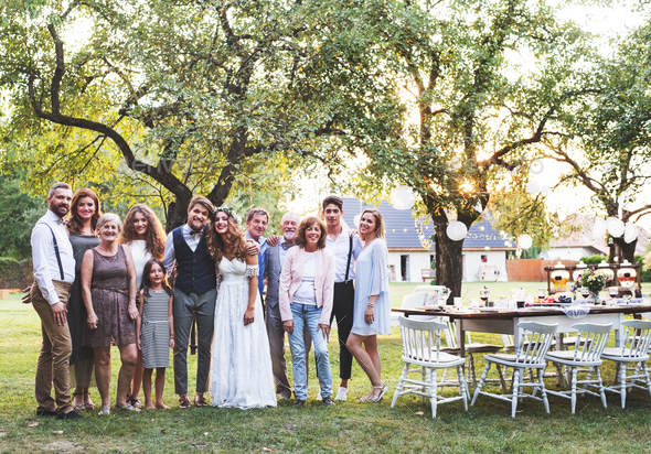 Bride, groom, guests posing for the photo at wedding reception outside in the backyard. - Stock Photo - Images