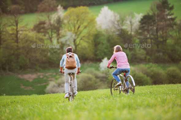 Beautiful senior couple with bicycles cycling outside in spring nature. - Stock Photo - Images
