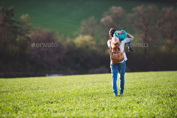A father with his toddler son on a walk outside in spring nature. - Stock Photo - Images