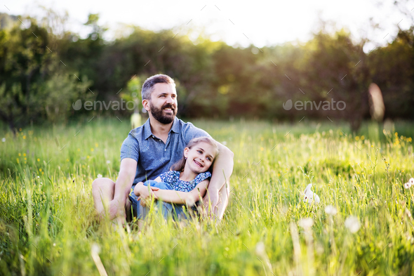 Father with a small daughter sitting on the grass in spring nature. - Stock Photo - Images