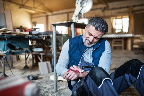Man with an injured hand after accident at work in the carpentry workshop. - Stock Photo - Images
