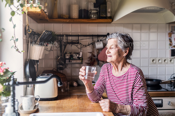 An elderly woman standing in the kitchen, holding a glass of water. - Stock Photo - Images
