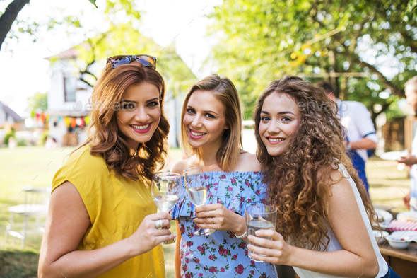 Portrait of three women on a family celebration or a barbecue party outside in the backyard. - Stock Photo - Images