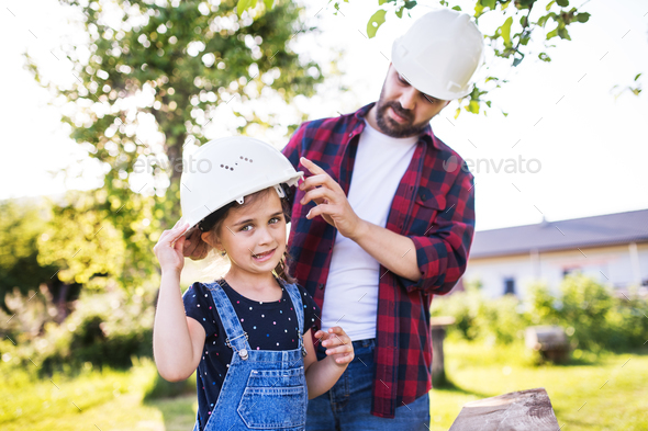 Father with a small daughter having fun with helmets in garden. Spring nature. - Stock Photo - Images