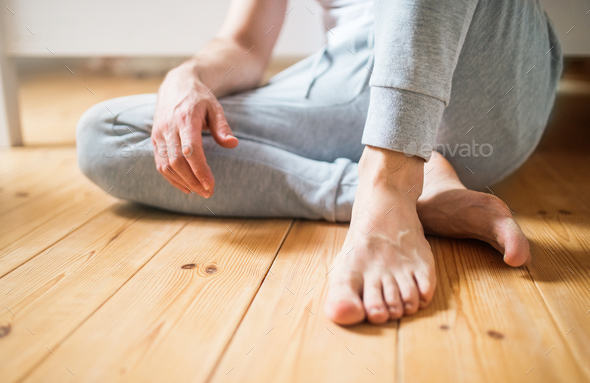 Unrecognizable man sitting on the floor in bedroom at home. - Stock Photo - Images