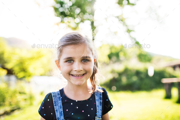 A portrait of a small girl in the garden in spring nature. - Stock Photo - Images