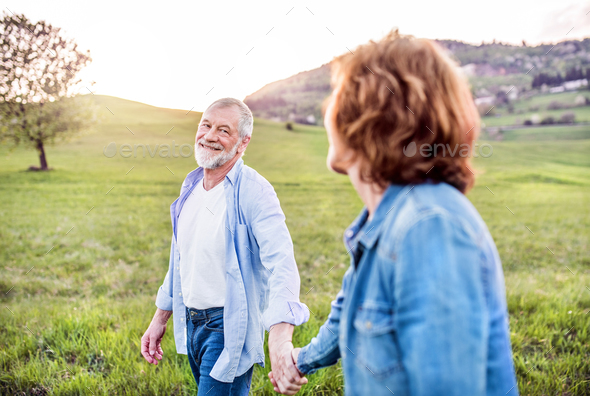 Senior couple walking outside in spring nature, holding hands. - Stock Photo - Images