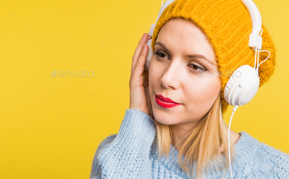 Portrait of a young beautiful woman with headphones in studio on a yellow background. - Stock Photo - Images