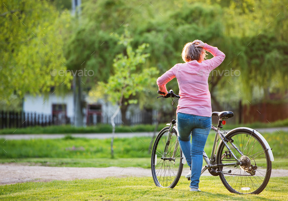 Senior woman with bicycle outside in spring nature. - Stock Photo - Images