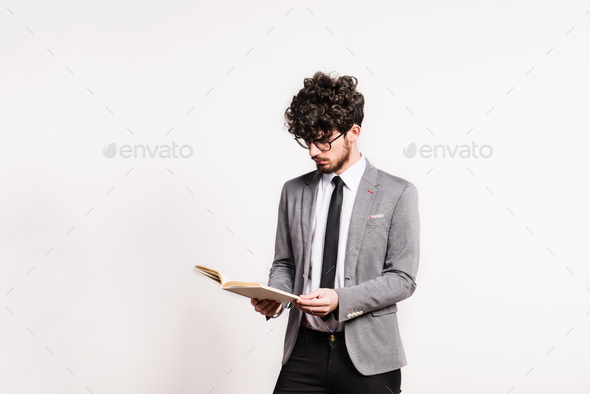 Portrait of a young man with a book in a studio on a white background. - Stock Photo - Images