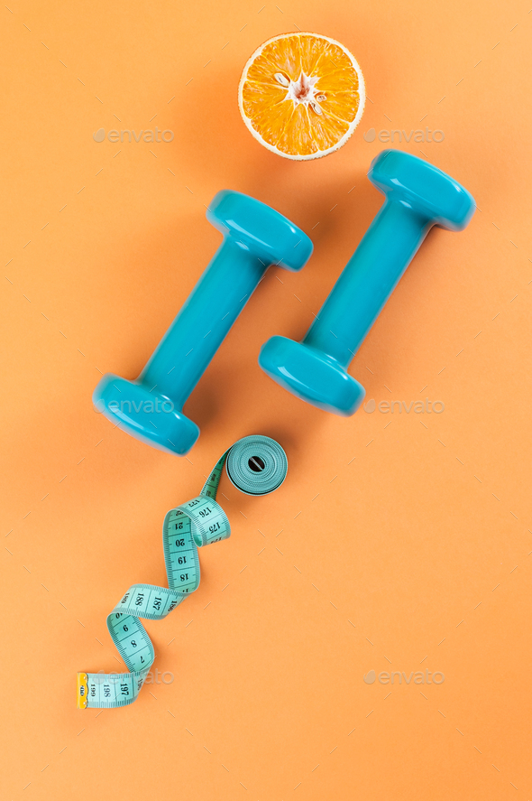 Dumbbells, a centimeter and half an orange on a light orange bac - Stock Photo - Images