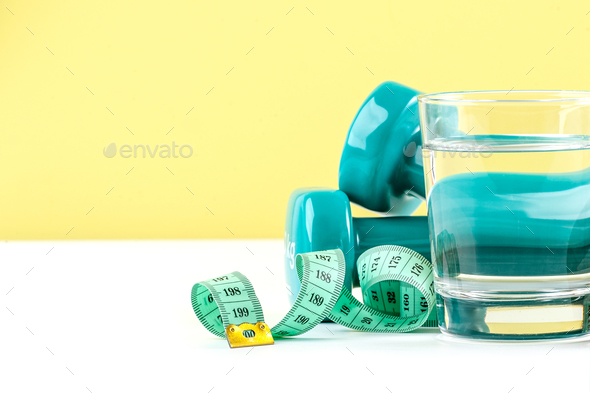 Dumbbells, centimeter and a glass of water on a white-green back - Stock Photo - Images