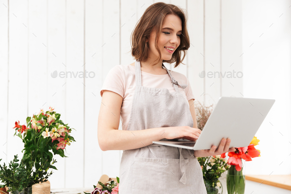 Beautiful sales woman standing near bouquets in flower workshop, - Stock Photo - Images