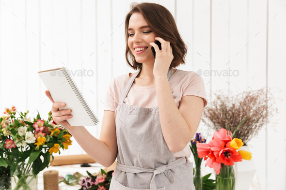 Happy florist woman in apron working in flower shop, and speakin - Stock Photo - Images