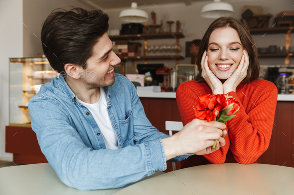 Photo of attractive man giving flowers to his beautiful woman, w - Stock Photo - Images